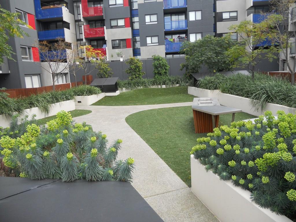 המתכננים לא יצרו שום מרחב ציבורי המאפשר אינטראקציה יומיומית בין התושבים. הגינה הפרטית בין שלושת הבניינים. המרפסות מקדימה הן של דיירי הדיור הציבורי (צילום: איריס לוין)