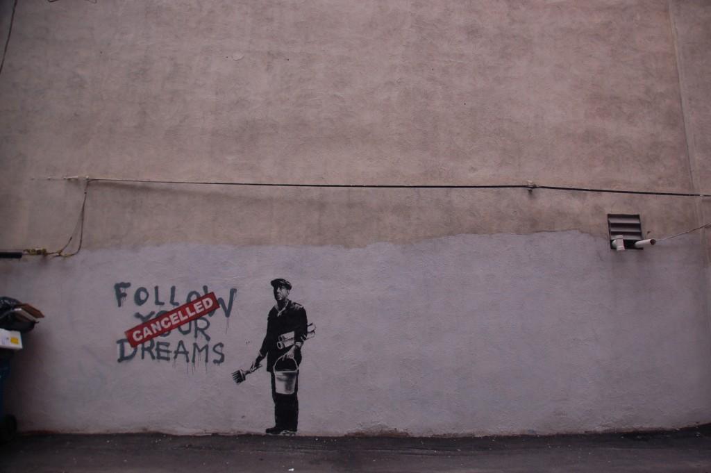 """""""העיסוק שלנו בצדק, ובחוסר צדק, צריך להיות לא רק 'אקדמי', אלא גם להוביל לקידום שינוי ממשי לטובה"""". כתובת גרפיטי של בנקסי בבוסטון (צילום: Chris Devers, Flickr.com)"""