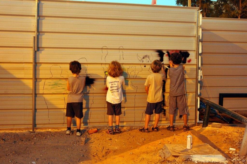 ילדי שכונת שפירא מציירים על הגדר של אתר הבנייה לדיור בר השגה שמיועד לאוכלוסיה חזקה שתגיע מבחוץ (צילום: שפי פז)