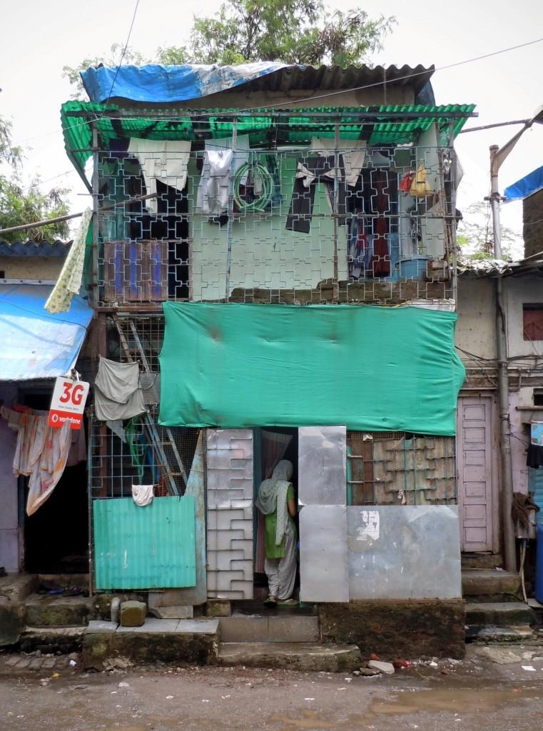בנייה בשלבים ותוספות אופיינית למגורים א-פורמאליים, כאן כפי שפלשה לדרך מהטמה גנדי בדרבי (Dharavi), מומבאי, הודו. באדיבות סיטסה דה מאאט (מתוך התערוכה)