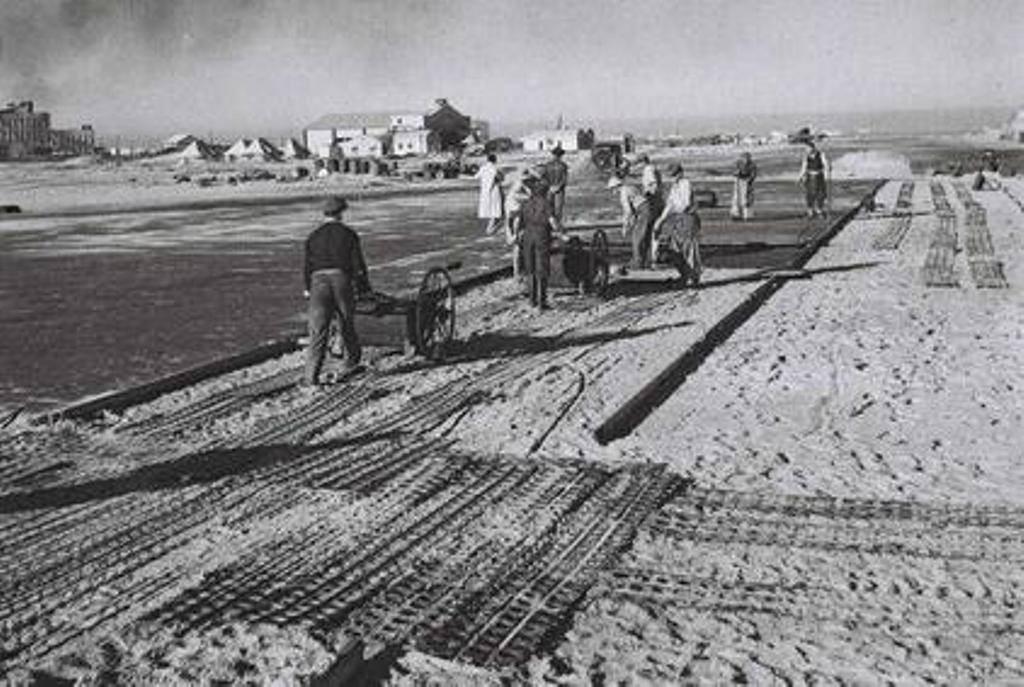 פועלים סוללים את מסלול ההמראה של שדה התעופה שדה דב. ברקע - בניית תחנת רידינג 1938 (צילום: זולטן קלוגר, פיקוויקי)