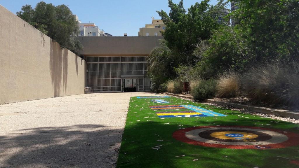 """הבנין מציע שתי """"נחמות"""" – האחת כבר בכניסה - צמחיה שמציצה מעל הקיר המרכזי המלווה את הכניסה לבניין (צילום: המעבדה לעיצוב עירוני)"""