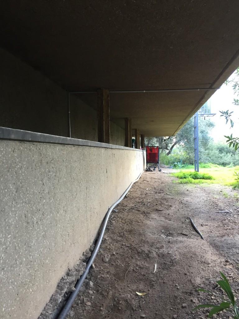 בגומחת החלון השקוע, המייצרת מעין מדף מוגן ומקורה נמנם לו חסר בית, ולידו מונחים חפציו.(צילום: טולה אמיר)