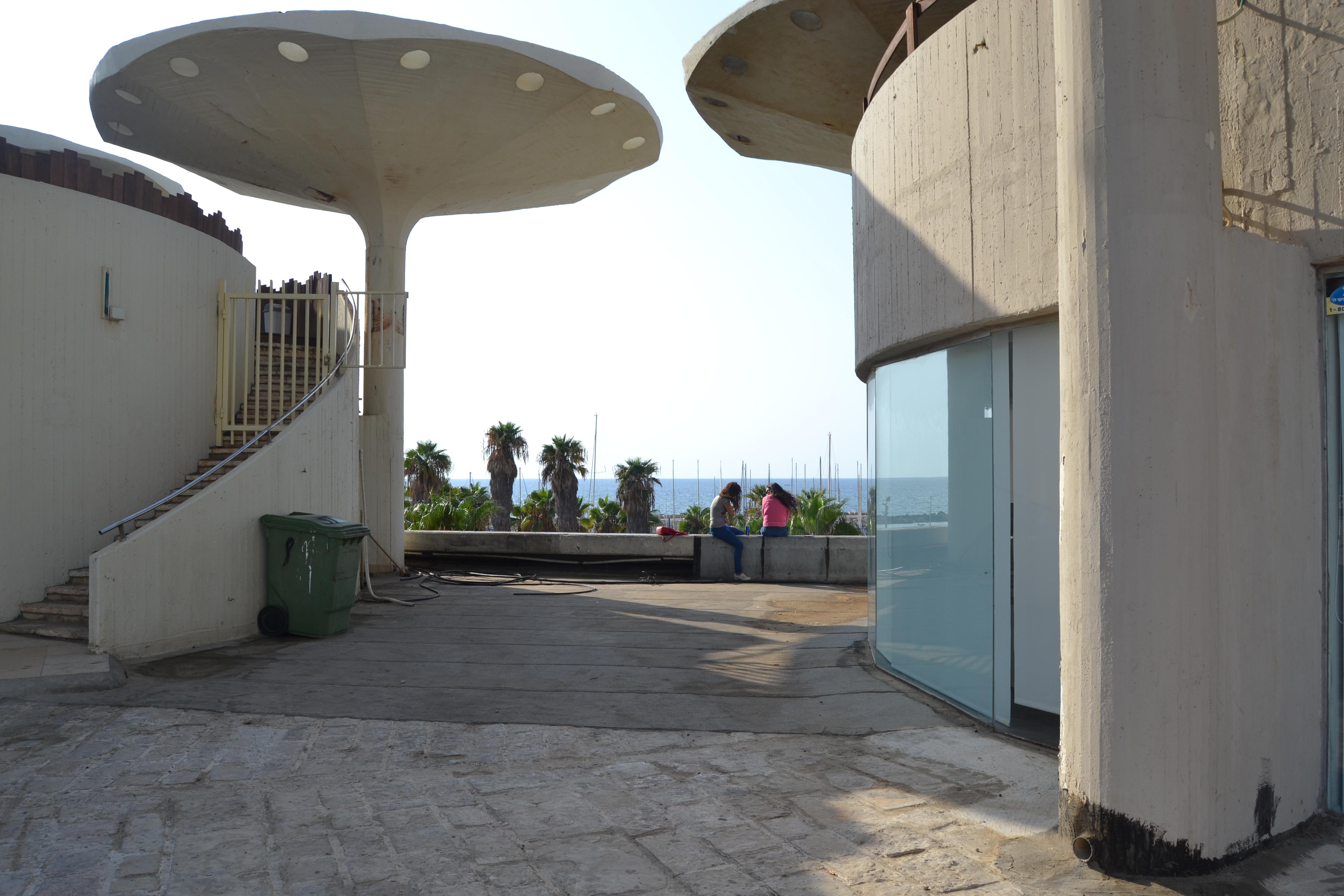 אינה מאפשרת מילוט זמני מהמולת העיר ומהקפיטליזם הצרכני. כיכר אתרים, תל אביב. איור: שלי חפץ