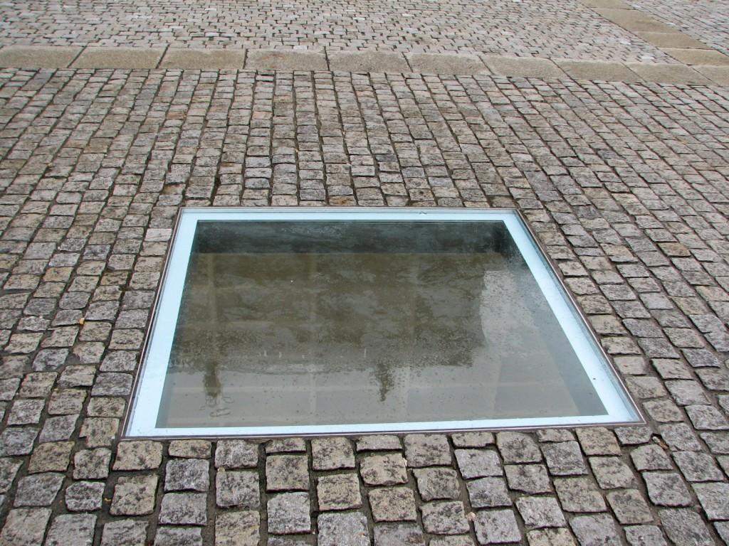 """""""הספרייה נפתחת אל ההווה דרך הסביבה המשתקפת בזכוכית"""". האנדרטה """"הספריה"""", של מיכה אולמן, בברלין (צילום: טלי חתוקה)"""