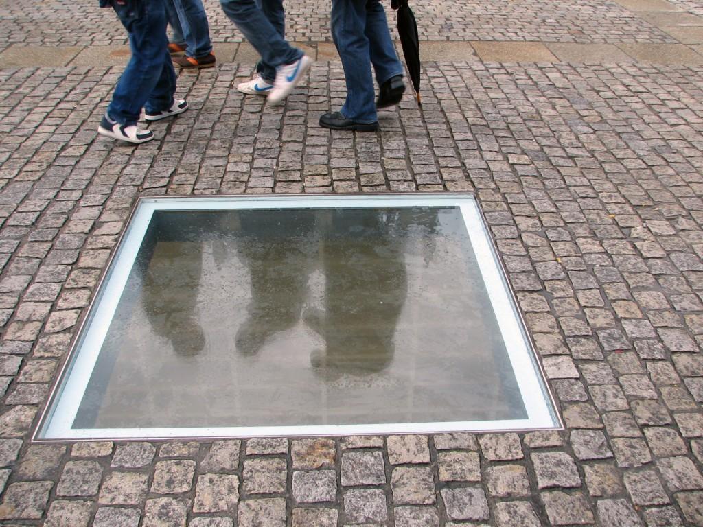 """יש מי שיביט פנימה ויצפה בדמותו המשתקפת. וכך ימצא עצמו בתוך הבור וייעשה חלק מן האנדרטה. האנדרטה """"הספריה"""", של מיכה אולמן, בברלין (צילום: טלי חתוקה)"""