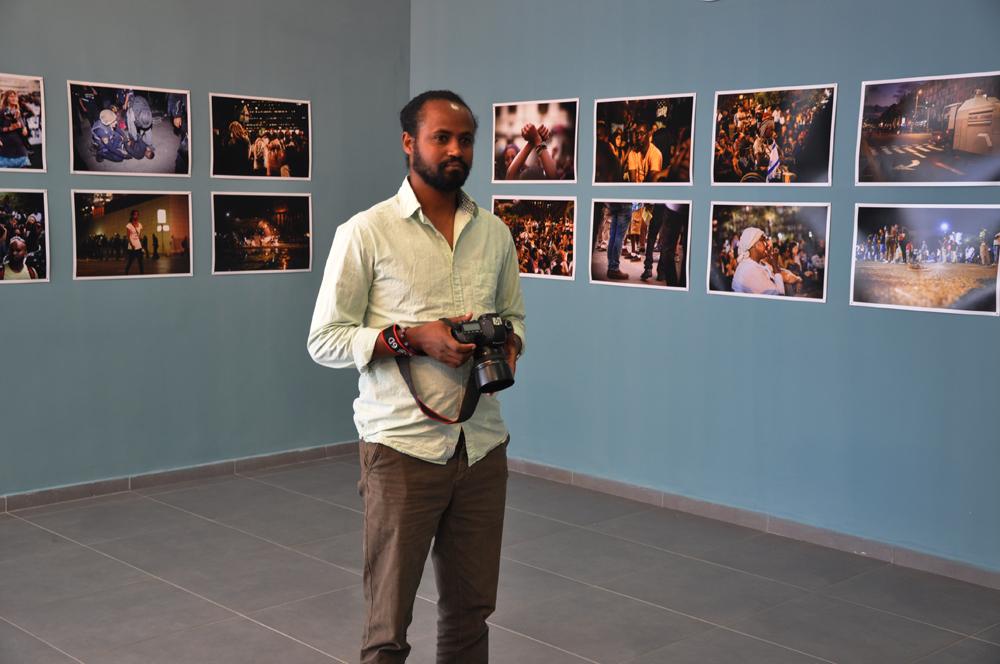 גדעון אגז'ה על רקע התצלומים בתערוכה (צילום: יונתן גת)