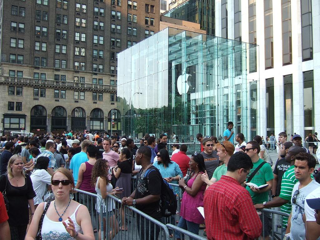התור מחוץ לחנות של אפל בניו יורק לפני יציאת האייפון החדש. אפל מייצרת עבורנו צרכים כוזבים חדשים שמשאירים אותנו בתוך המרדף ומגבירים את המרוץ והחיבוריות המתמדת (צילום: Rob DiCaterino from Jersey City, NJ, USA Wikimedia)